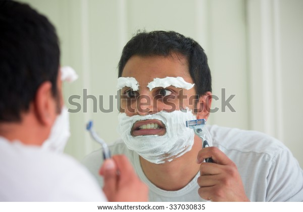 Closeup portrait, overzealous mentally deranged, mad as a hatter, young man at the end of his rope, attempting to shave his face eyebrows and face, isolated window reflection