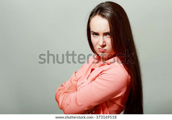Closeup portrait, pangry, grumpy, skeptical young woman with bad attitude, arms crossed, looking at you isolated grey background. Negative human emotion, facial expressions, feelings