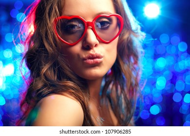 Close-up portrait of a partying girl wearing heart-shaped sunglasses