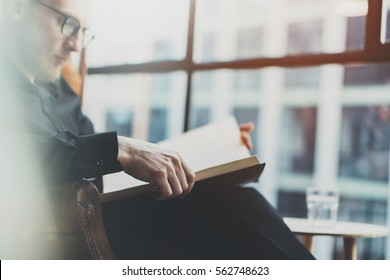 Closeup portrait of pensive bearded businessman reading book while sitting in vintage chair.Young man relaxing at home.Selective focus on hands,blurred background.Horizontal, film effect