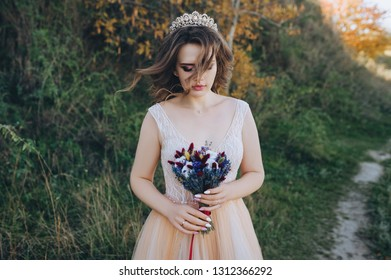 Closeup portrait of a pensive bride with brown hair in a beige dress with a crown on her head. The bride in love with a bouquet on nature. Wedding photography. The wind blows hair.