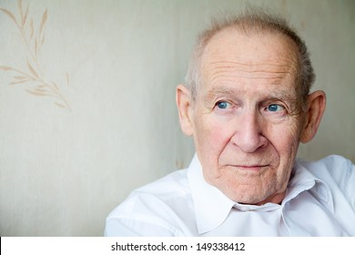 close-up portrait of a pensive senior man, he is looking somewhere
