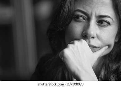Close-up portrait of a pensive woman. Black and white.