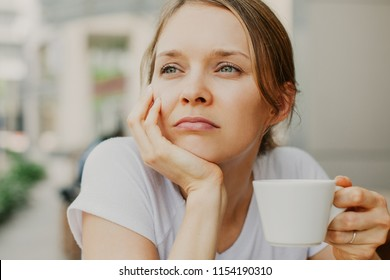 Closeup portrait of pensive young beautiful woman drinking coffee outdoors with blurred street view in background. Front view.
