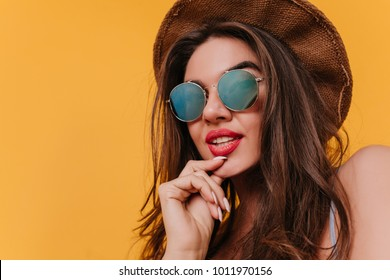 Close-up portrait of pensive young woman in sparkle sunglasses. Studio shot of lovable dark-haired girl wears vintage brown hat.