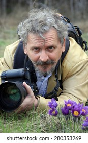 Close-up portrait photographer lying on the meadow, making pictures of flowers in spring