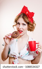 closeup portrait of pinup girl beautiful blond young woman with excellent dental care teeth having fun eating donut and drinking coffee looking at camera on white background