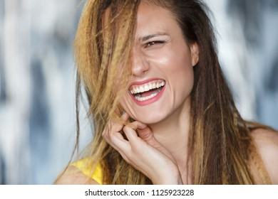 Close-up portrait - playful young woman with a contagious smile looking away. Charming student with a disheveled hairdo smiles broadly
