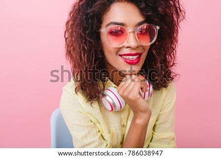 Close-up portrait of pleased brunette girl with bronze skin touching chin with hand. Indoor photo of smiling african female model in stylish pink glasses.