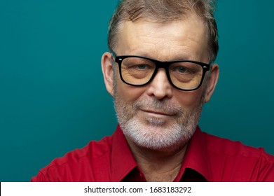 Close-up portrait of a positive elderly handsome man in glasses posing on a dark green background. The concept of a successful man. Copyspace