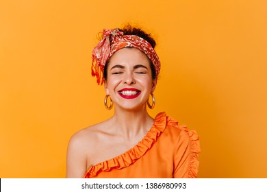Close-up portrait of positive woman with red lips dressed in blouse with bare shoulder and headband laughing with closed eyes on isolated background