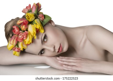 close-up portrait of pretty blonde girl with naked shoulders, lying on a table wearing spring floral garland and looking in camera