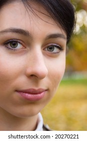 Closeup portrait of a pretty brunette girl in an autumn park