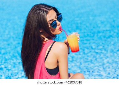Close-up portrait of pretty brunette girl with long hair sitting on water background. She wears pink T-shirt, shorts, sunglasses. She is drinking cocktail through straw. View from back.