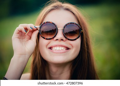 Close-up portrait of a pretty brunette in sunglasses round glasses. The girl smiles, she holds the right hand edge of the glasses. Outdoors.
