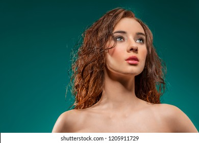 close-up portrait of pretty brunette woman with wavy and wet hair-style, red make-up and naked shoulders on green