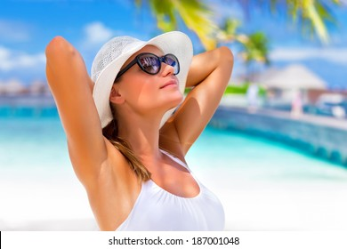 Closeup portrait of pretty girl with hands behind head enjoying sunlight, tanning on tropical beach, luxury spa resort, travel and tourism concept
