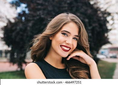 Closeup portrait of pretty girl with long curly hair on street on black trees background. She wears black dress, red lips. She is touching face and smiling to camera.