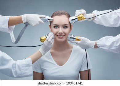 closeup portrait of pretty happy young woman and hands in gloves holding medical maniples touching her face