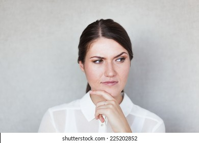 Closeup portrait of pretty mad young woman, finger on lips, daydreaming something serious and upsetting. Human facial expressions, emotions, feelings, signs, symbols