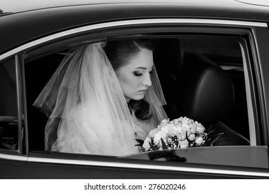 close-up portrait of a pretty shy bride in a car window.