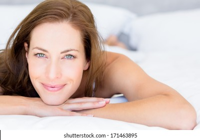 Close-up portrait of a pretty smiling young woman lying in bed at home