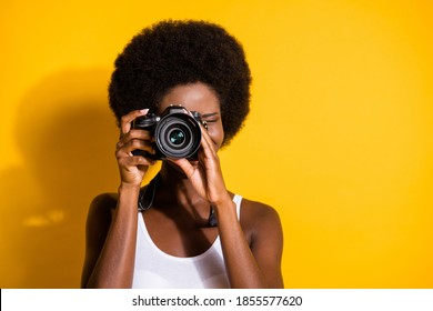 Close-up portrait of pretty wavy-haired brunette girl using digicam taking pictures snap isolated over bright yellow color background