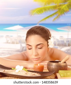 Closeup portrait of pretty woman lying down on massage table on the beach, closed eyes, luxury spa resort, tropical vacation, summer holidays