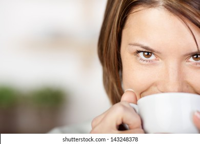 Close-up portrait of a pretty woman smiling and drinking coffee.