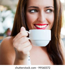 Closeup portrait of a pretty young female having a cup of coffee