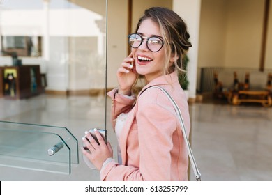 Closeup portrait of pretty young woman with hair up entering building, glass door into office, hotel, business centre. Wearing fashionable glasses, gray pants, pink jacket.