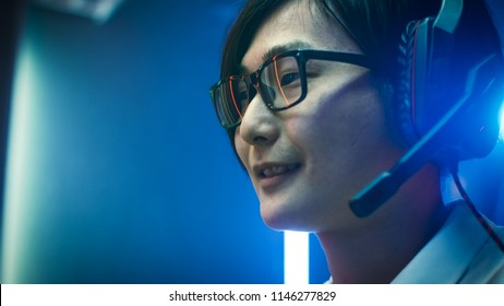 Close-up Portrait of the Professional Asian Gamer Playing in Online Video Game, He's wearing Glasses, talks/ chats with His Teammates / Friends through Headphones. Neon Colored Room. eSport Cyber Game
