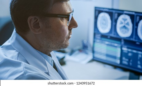 Close-up Portrait of Professional Doctor Looking at MRI or CT Scan Images on His Computer Monitor, Searching for Signs of Brain Tumor or Cancer, Trying to Diagnose Disease.