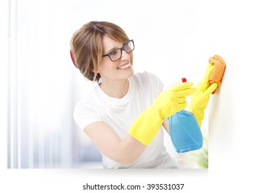 Close-up portrait of professional domestic worker woman cleaning white surface.
