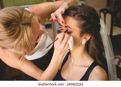 Closeup portrait of professional makeup artist applying mascara