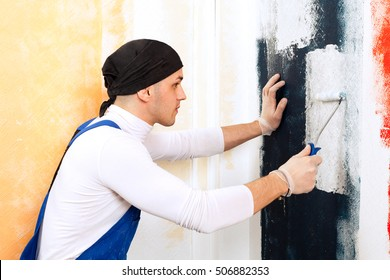 Close-up portrait of professional painter work man in gloves and working clothes by work of whitewashing with small roller in a office room