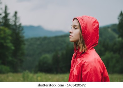 Closeup portrait in profile of attractive girl in red raincoat stands against the background of mountains and coniferous forest in cloudy rainy weather, looking away with serious face.