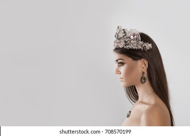 Closeup portrait in profile Beauty queen pageant winner girl with tiara long hair lipstick and eye shadows matching with dark crystal diamond earring necklace and crown looking to side on white grey