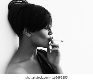 Close-up portrait in profile of a girl with a cigarette and a cool hairstyle , black and white
