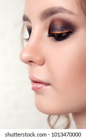 Close-up portrait in profile of a girl with a professional makeup on the eyes close  up