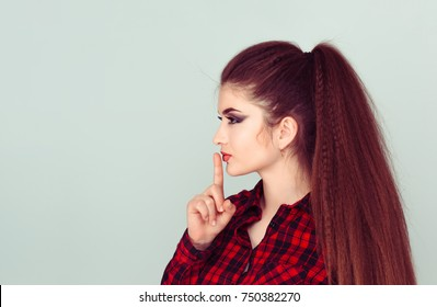 Closeup portrait profile view secretive young woman placing finger on lips asking shh, quiet, silence looking sideways isolated light green background. Human face expression sign emotion body language