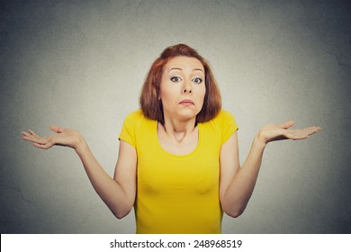 Closeup portrait puzzled clueless young woman with arms out asking what is problem who cares so what I don't know isolated grey background. Negative human emotion face expression reaction perception