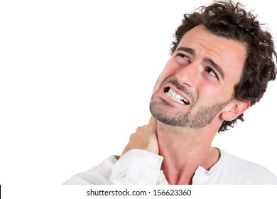 Closeup portrait of really stressed unhappy young handsome man with really bad neck pain, after along hours of work or studying, isolated on white background with copy space