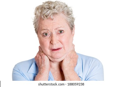 Closeup portrait, really stressed unhappy, senior mature woman with bad neck spasm pain, after long hours of work, studying, isolated white background. Negative human emotions, facial expressions