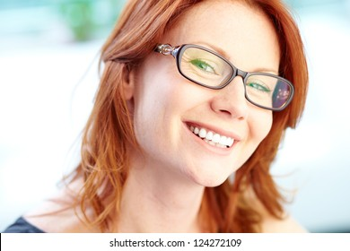 Close-up portrait of a red-haired female smiling with confidence