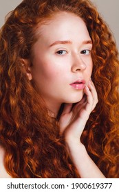 close-up portrait of a red-haired girl with brown eyes and long curly hair and small freckles without makeup. Studio shot