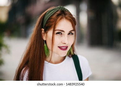 Close-up portrait of a red-haired girl in the city