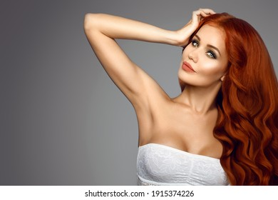 Close-up portrait red-haired woman with her hand raised, long curly shiny hair. Armpit removal sugaring wax removal. Beauty girl smile laugh isolated on grey background
