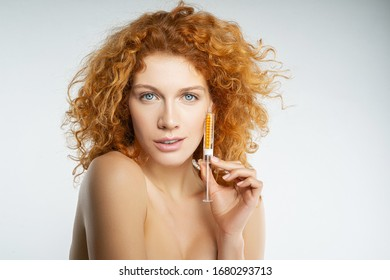 Closeup portrait of a red-haired woman showing a serum syringe in front of the camera