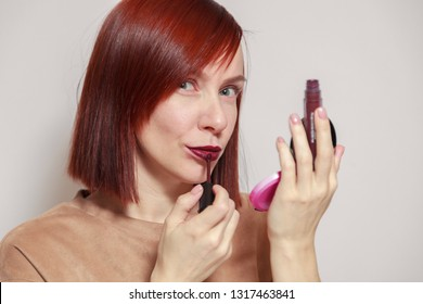 Closeup portrait redhead beautiful girl looking in mirror of compact powder and paints lips with dark burgundy purple liquid lipstick. Concept makeup school, future makeup artist, get ready for party
